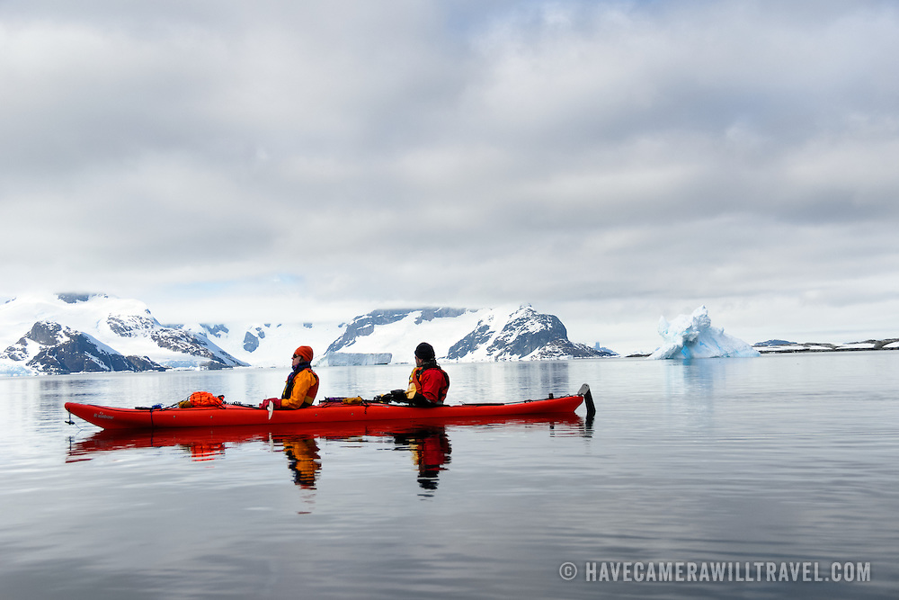 Kayakers in a tandem kayak glide over glassy still waters at Petermann Island on the Antarctic Peninsula.
