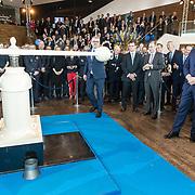 NLD/Amsterdam/20190314  - Koning bij viering 100 jaar Luchtvaart  in Nederland, Koning Willem Alexander  slaat het eerste herdenkingsmuntje