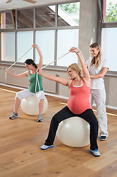 Female fitness trainer pregnant woman Pilates ball