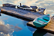 Dinghies sit beside a dock in a bay in Addison, Maine.