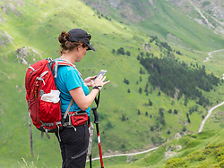 Woman hiker using mobile phone in the High Pyrenees, Gavarnie, France
