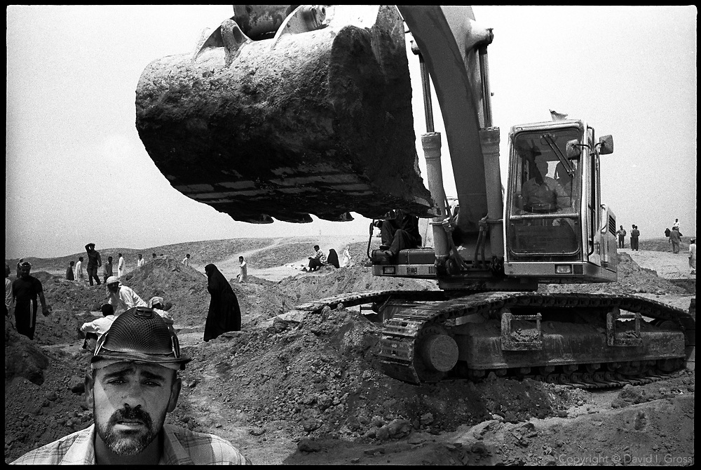 Iraqis search a mass grave site for remains using a large digger in a frantic search to find long-missing relatives near Hillah, Iraq. The chaotic digging caused such destruction of evidence -- of both crimes against humanity and of identity -- that Human Rights Watch began a campaign to embarass the U.S. military into closing the site.