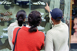 Single mother with teenage daughter and son looking at shop window display in town centre,