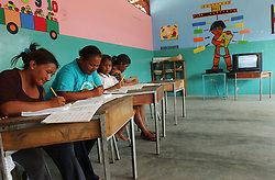 """Students take part in Plan Robinson literacy classes in a small jungle village.  President Chavez aims to erradicate illiteracy in Venezuela through Plan Robinson,  which uses lessons and cassetes created in Cuba.  Critics of the program claim that the classes are primarily used as a tool of political indoctrination as part of Chavez's plan to """"Cubanize"""" Venezuela."""