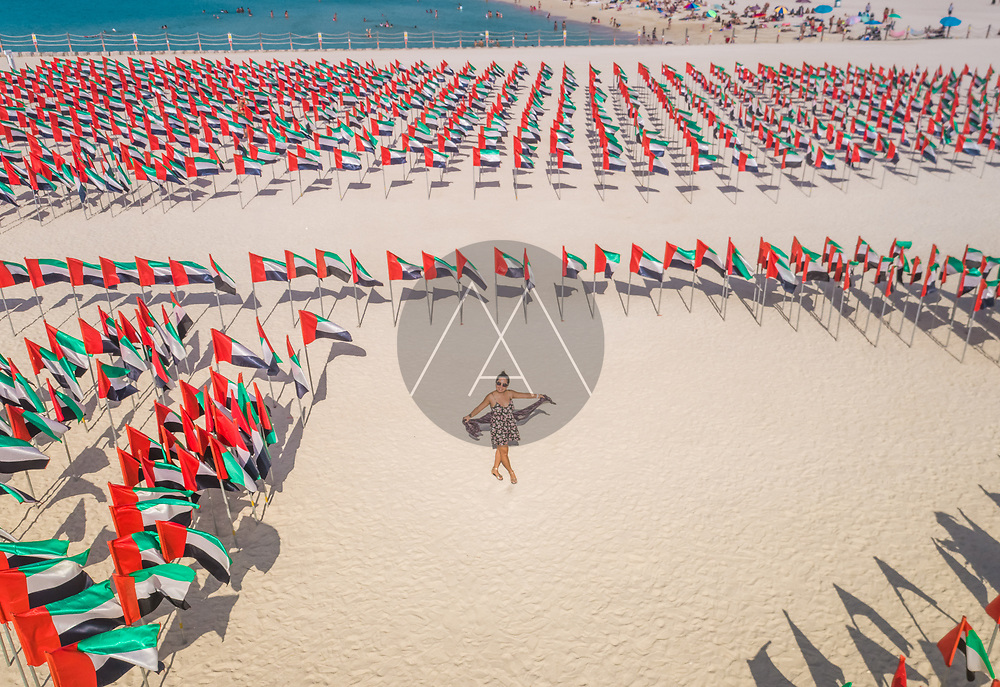 Aerial view of a woman in the middle of national flags of U.A.E on a sandy beach in Dubai.