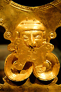 Pectoral Ornament.  Colombia; Yotoco (Calima) 1st - 7th century.  Hammered gold.  The human face in the centre of such pectorals was created by hammering the metal over a carved former, probably made of wood, in a process called embossing.