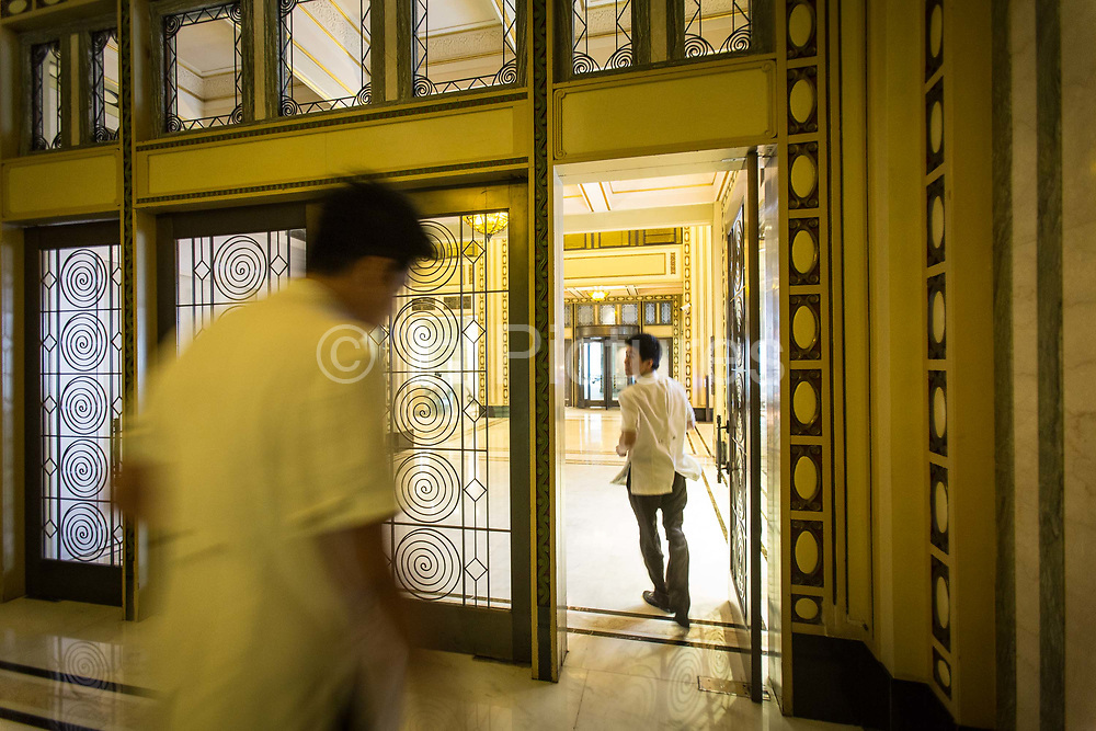 Two men walk through Sir Victor Sassoons Cathay Hotel renamed the Peace Hotel, now locked due to Fengshui reasons, in Shanghai, China on September 21, 2014. Sassoon was a jewish tycoon that left a series of buildings that once dominated the city of Shanghai in the 1920s and 30s.