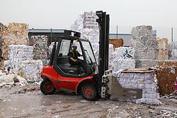 Forklift driver lifting waste paper bale,