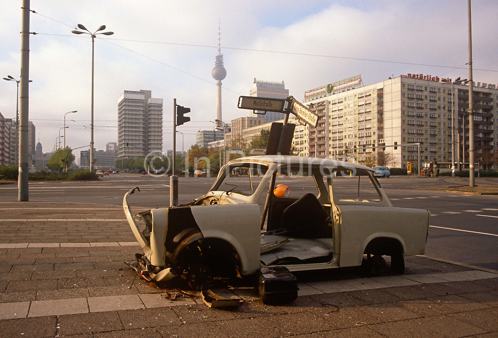 Six months after the fall of the Berlin Wall, a Trabant car sits wrecked on the corner of Mollstrasse and Hans-Beimler-Strasse in east Berlin former DDR, on 1st June 1990, in Berlin, Germany. The DDR-produced Trabant suffered poor performance, but its smoky two-stroke engine regarded with affection as a symbol of the more positive sides of East Germany. Many East Germans streamed into West Berlin and West Germany in their Trabants after the opening of the Berlin Wall. It was in production without any significant change for nearly 30 years. The name Trabant means fellow traveler in German.