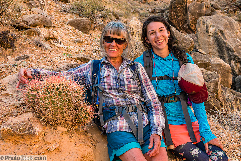 Arizona Raft Adventures (AZRA) trip leader Lorna Corson hugs a cactus next to assistant guide Bekah Martin. Hike to the prehistoric Nankoweap Granaries (1 mile round trip with 700-foot gain) from Main Nankoweap Camp at Colorado River Mile 53.4 in Marble Canyon. This image is from Day 3 of 16 days boating 226 miles down the Colorado River in Grand Canyon National Park, Arizona, USA. For this photo's licensing options, please inquire at PhotoSeek.com. .