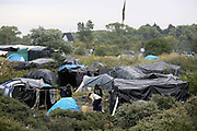 Tent city 'the Jungle' migrant camp in Calais, France, August 10, 2015. The Calais jungle is the nickname given to a series of camps in the vicinity of Calais, France, where migrants live while they attempt to enter the United Kingdom illegally by stowing away on lorries, ferries, cars, or trains travelling through the Port of Calais or the Eurotunnel Calais Terminal. The migrants are a mix of refugees, asylum seekers and economic migrants from Darfur, Afghanistan, Syria, Iraq, Eritrea and other troubled areas of the world.