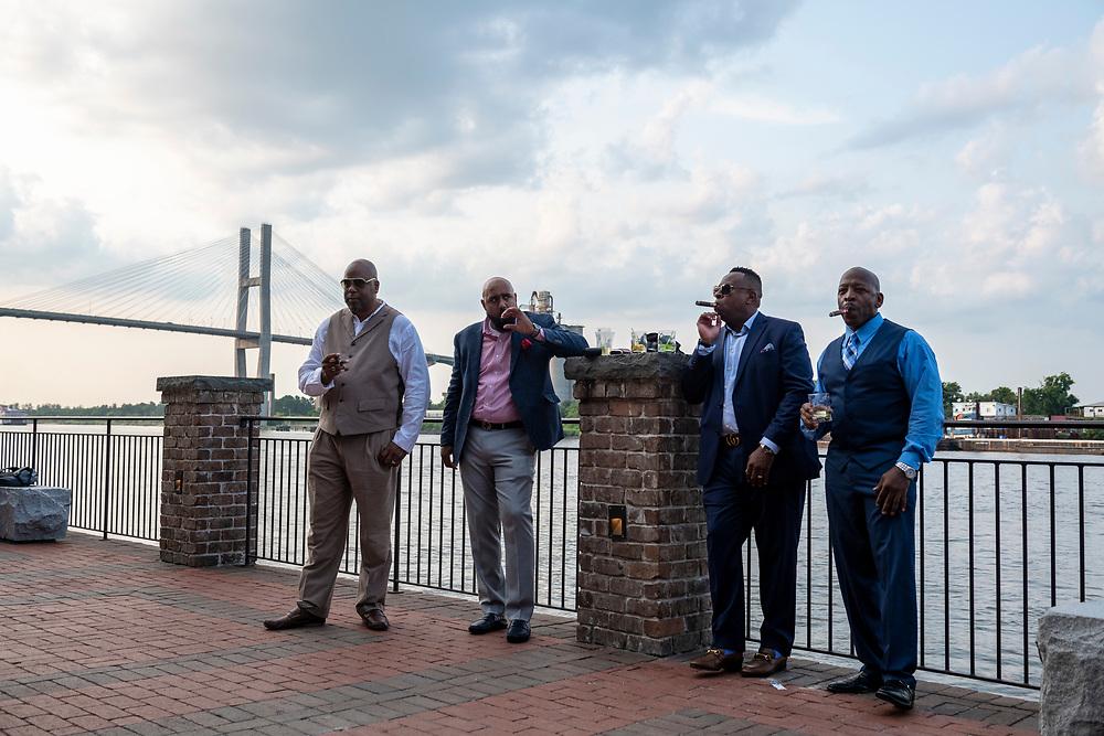 Savannah, Georgia - July 30, 2021: Kevin Thomas, Theeo Zamora, Reggie Moore, and Anthony Prescott smoke cigars and enjoy a Friday evening at the Plant Riverside district on Savannah's riverfront