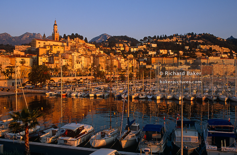 "The pretty coastal town of Menton on the French Cote d'Azur is seen beneath a cloudless blue sky in later afternoon spring sunshine. Looking across the water, in the foreground is the marina populated with assorted yachts, launches and other boats safely moored to jetties and pontoons. The bell-tower of baroque basilica Saint-Michel-Archange, houses and buildings of Menton rise up along hillsides and the mountains of the Ligurian Alps rise up in the distance, all bathed in orange light. Mediterranean Menton - near the Italian border - is known as Le perle de la France (""The Pearl of France"") for its famous beauty. It is also known for La Musée Jean Cocteau which is located in the town."