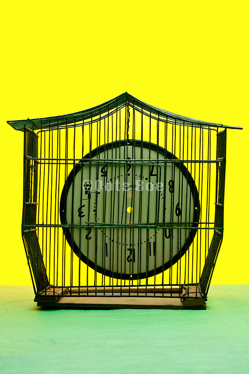 empty bird cage with upside down clock plate without dial