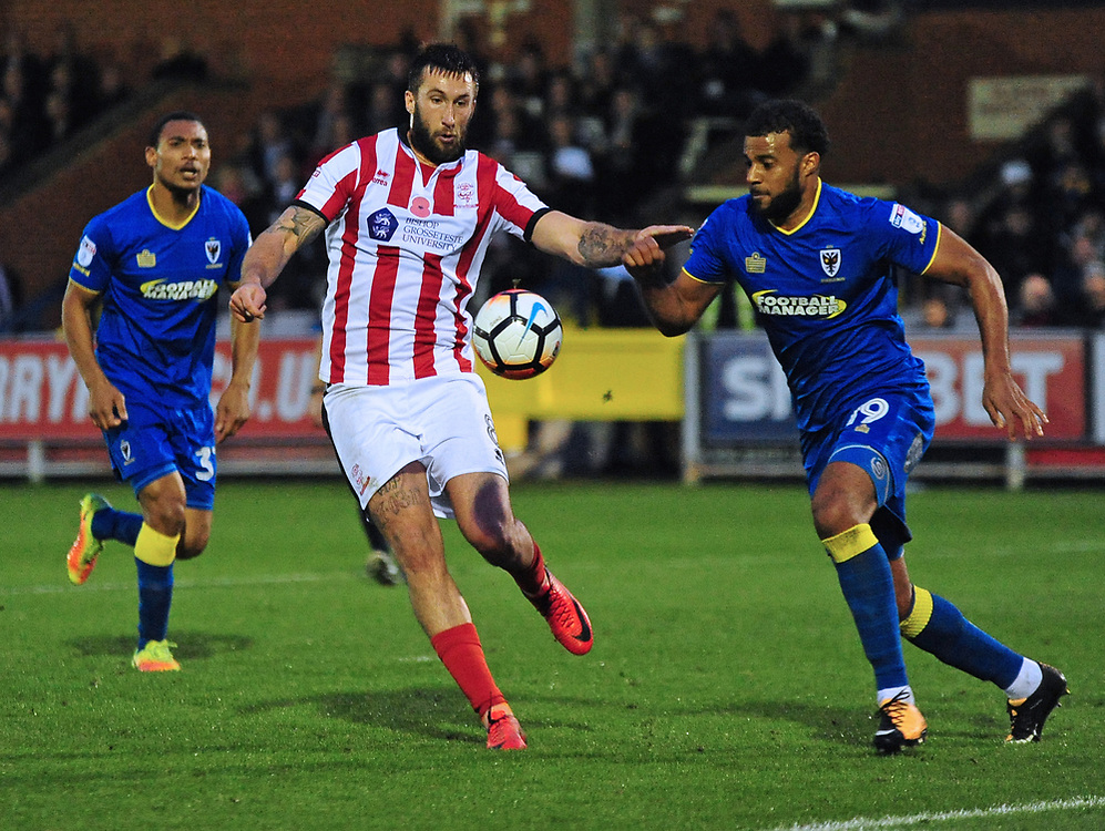 Lincoln City's Ollie Palmer vies for possession with AFC Wimbledon's Tom Soares<br /> <br /> Photographer Andrew Vaughan/CameraSport<br /> <br /> Emirates FA Cup First Round - AFC Wimbledon v Lincoln City - Saturday 4th November 2017 - Kingsmeadow Stadium - London<br />  <br /> World Copyright © 2017 CameraSport. All rights reserved. 43 Linden Ave. Countesthorpe. Leicester. England. LE8 5PG - Tel: +44 (0) 116 277 4147 - admin@camerasport.com - www.camerasport.com