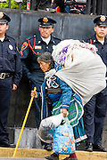 16 SEPTEMBER 2005 - MEXICO CITY: A homeless woman walks past Mexico City police officers during the   Independence Day parade in Mexico City, Sept. 16. Mexico celebrated its 195th Independence Day in 2005 with a huge military parade through the center of Mexico City.  PHOTO BY JACK KURTZ