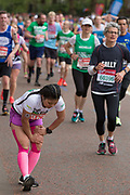 A lady stretching her legs on Birdcage Walk during The Virgin London Marathon on 28th April 2019 in London in the United Kingdom. Now in it's 39th year, the London Marathon is a large sporting event with over 40,000 runners expected to take part.
