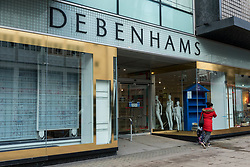 © Licensed to London News Pictures. 28/01/2021. LONDON, UK. Mannequins stand at the entrance as a woman passes the exterior of Debenhams department store on Oxford Street, the traditional home of retail in the West End. The windows and shop floor of the store have already been cleared of stock. Online retailer Boohoo has recently purchased the Debenhams brand, all stores will close and 12,000 staff will lose their jobs.    Photo credit: Stephen Chung/LNP