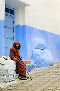 Morocco, Chefchaouen. Man wearing a traditional jellaba resting near the blue door.