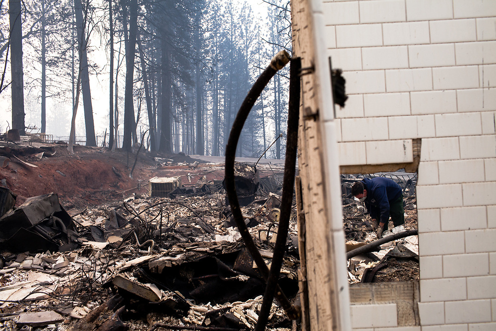 A resident searches through rubble of his home after the Camp Fire ripped through Paradise, California, Thursday, November 15, 2018. The fire burned a total of more than 153,000 acres throughout Butte County.