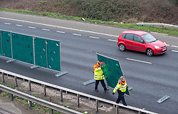 © Licensed to London News Pictures. 05/01/2019. Westend, Gloucestershire, UK. Emergency services remove a screen as traffic passes northbound at the scene of a fatal accident this morning when a pedestrian was killed after being in collision with a vehicle on the southbound carriageway. A yellow chalk circle is visible on the carriageway close to a drain with a visible area of stained earth at the edge of the fast lane. The M5 was closed in both directions for several hours. Photo credit: Simon Chapman/LNP