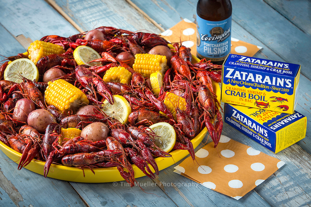 Boiled crawfish with corn and potatoes in a tray served with cold Covington Brewhouse beer.