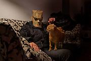 Man wearing cardboard mask stroking a cat