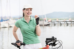 Mature woman eating an apple at lakeside and smiling, Bavaria, Germany