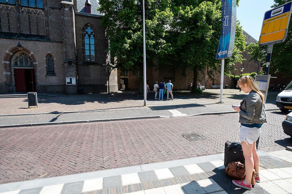 Bij het Catherijneconvent in Utrecht kijkt een jong meisje naar haar mobiele telefoon terwijl ze bij een bushalte wacht met haar koffer.<br /> <br /> Near the Catherijneconvent in Utrecht a young woman is checking her mobile phone while waiting at the bus stop with her suitcase.
