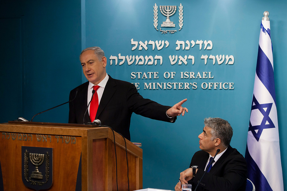 Israel's Prime Minister Benjamin Netanyahu (L) gestures as he speaks while Israel's Minister of Finance Yair Lapid (R) listens, during a press conference in which they presented a new planned sea ports reform in Israel, at the Prime Minister's Office in Jerusalem, on July 3, 2013. The Israeli government initiated a tender for two new private ports to operate beside existing government-owned ports in Haifa and Ashdod in a bid to raise competition, break the monopoly in the current system and lower the costs of good in Israel.