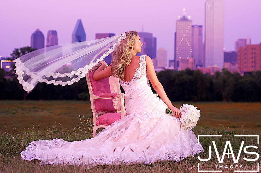 Wind blowing the veil of a bride in her white dress sitting in a pink chair overlooking downtown Dallas at sunset.