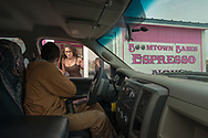 Elias Angulo,orders coffee from Shannon Kobzina, at Boomtown Babes Espresso drive through coffee hut in Williston, N.D., Oct 3, 2013. Owner Nyssa Gray opened the coffee hut August 6. Gray managed Hot Chick-a Latte in Seattle, WA for five years before moving to Williston.