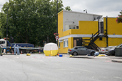 © Licensed to London News Pictures. 08/08/2017. LONDON, UK.  Forensic officers and a forensic tent within the crime scene cordon on the corner of Old Kent Road and Ilderton Road, next to the Afrikiko Bar Restaurant and Club. Police were called at around 2am and found a 19 year old man with stab injuries, who was pronounced dead about an hour later. Five people have now been arrested in connection with stabbing and are being held at a south London police station.  Photo credit: Vickie Flores/LNP