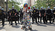 An anti-NATO protester and member of the Clown Bloq stands in front of Chicago police offers as the protesters march along Michigan Avenue in the South Loop on Sunday, May 20, 2012. (Brian Cassella/Chicago Tribune)  B582116857Z.1<br /> ....OUTSIDE TRIBUNE CO.- NO MAGS,  NO SALES, NO INTERNET, NO TV, CHICAGO OUT, NO DIGITAL MANIPULATION...