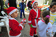Israel, Haifa, Wadi Nisnas, Children dressed up as Santa Claus in a parade during the Holiday of holidays festival, celebrating Hanuka-Christmas-Ramadan December 2009