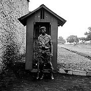 A Congolese soldier from FARDC stands guard outside Goma's FARDC Headquarters in 2008. FARDC in the region congregates in this HQ, attend military trainings, meetings, and even court hearings of various crimes committed by its soldiers.
