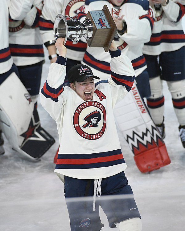 ERIE, PA - MARCH 06: Emily Curlett #5 of the Robert Morris Colonials hoists the CHA Championship Trophy after the Colonials defeated the Syracuse Orange 1-0 in the championship game at the Erie Insurance Arena on March 6, 2021 in Erie, Pennsylvania. (Photo by Justin Berl/Robert Morris Athletics)