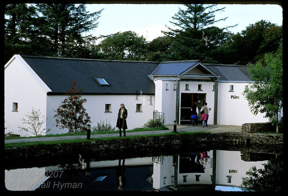 Woman pauses by pond in front of visitor center in Connemara National Park; Letterfrack, County Galway, Ireland.