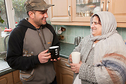 Portrait of South Asian woman and her son drinking tea and talking.