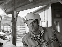 portrait of a rugged good looking cowboy on a ranch