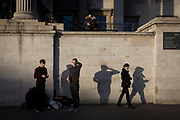 Young people whose shadows are on the wall of the National Portrait Gallery in Trafalgar Sq, London. The two young men have been busking in this famous London landmark, their act having just finished requiring them to change back into their own clothes on a winter's day. One of them squints into the sun, making a definite shape alongside his sidekick and an incidental woman, texting on her smartphone on the right. A couple hug each other above as someone else takes their picture with Westminster in the background. The wall belongs to the southern frontage of the National Portrait Gallery in Westminster.