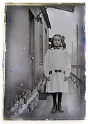 deteriorating glass plate of young girl standing