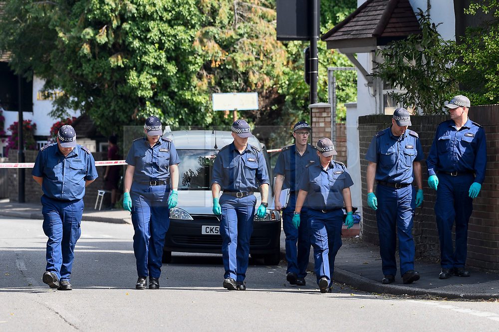 © Licensed to London News Pictures. 25/08/2019. SOUTHALL, UK.  Police officers conduct a search adjacent to St Mary's Avenue near Southall in west London.  It is reported that a man in his 60s was stabbed outside The Plough pub on Tentelow Avenue in the early evening of 24 August and stumbled to nearby St Mary's Avenue to seek aid from a residence.  Police were called at 6.41pm, paramedics and air ambulance crews attended but the man passed away.  A man in his 30s has been arrested on suspicion of murder.  The investigation continues. Photo credit: Stephen Chung/LNP