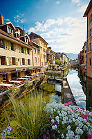 View of the Auberge du Lyonnais Hôtel/Restaurant and other buildings along the incredible reflective waters of the Thiou Canal, Old Town Annecy, France (Vertical).