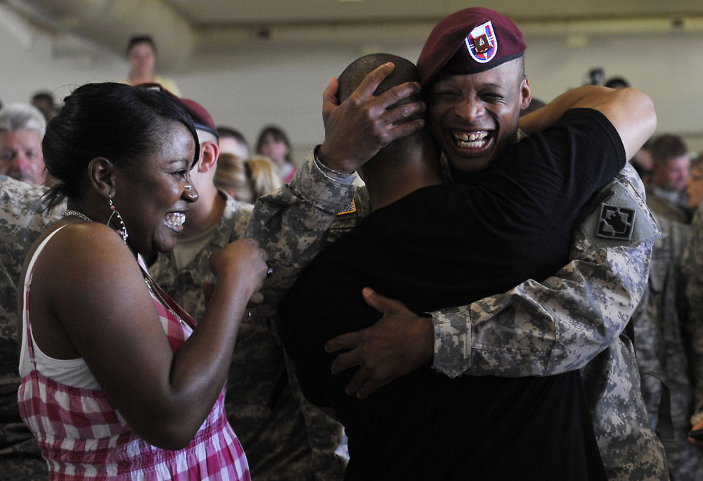 Nathaniel Williams, in red camos, embraces Sargent Eric Martinez, in black t-shirt, as his wife Tara Williams looks on. Homecoming of the the 37th Engineer Battalion on Friday, May 28, 2010.