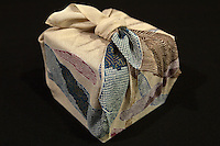 """Furoshiki are a type of traditional Japanese wrapping cloth that are used to transport clothes, gifts, or other goods. Dating back as far as the Nara period, the name furoshiki literally """"bath spread"""" derives from the Edo period practice of using them to bundle clothes while at the sento.  Furoshiki were known as hirazutsumi """"flat folded bundle""""  Eventually, the furoshiki's usage extended to serve as a means for merchants to transport goods.  Nowadays they are widely used to protect and decorate a gift, lunch boxes with hundreds of other practical uses."""