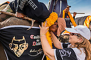 "28 AUGUST 2014 - BANGKOK, THAILAND:     A polo player hands her mahout a marigold flower garland before the King's Cup Elephant Polo Tournament at VR Sports Club in Samut Prakan on the outskirts of Bangkok, Thailand. Each elephant carries two people, the polo player and mahout, who actually controls the elephant. The tournament's primary sponsor in Anantara Resorts. This is the 13th year for the King's Cup Elephant Polo Tournament. The sport of elephant polo started in Nepal in 1982. Proceeds from the King's Cup tournament goes to help rehabilitate elephants rescued from abuse. Each team has three players and three elephants. Matches take place on a pitch (field) 80 meters by 48 meters using standard polo balls. The game is divided into two 7 minute ""chukkas"" or halves.  PHOTO BY JACK KURTZ"