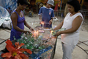 Women make flowers for the carnival from plastic bottles cut and melted on candles, Cubatão Samba School