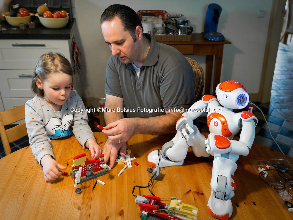 Nederland,  Biest-Houtakker, Lennart en zijn dochter Manou knutselen samen een lego robotje in elkaar op zaterdagochtend. Rechts in de hoek staat robot Zora bekend van tv docu's voor verzorgingshuizen.   telefoonnummer 0653804656