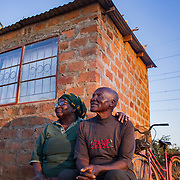 INDIVIDUAL(S) PHOTOGRAPHED: Theresa Nguluwe (left) and Brasford Nguluwe (right). LOCATION: Kuku Compound, Chitukuko, Chilanga District, Lusaka, Zambia. CAPTION: Theresa (left) and Brasford Nguluwe (right) at the home their granddaughter, Ruth Kampangele, built for them in Chitukuko, Lusaka. Ruth built their house after attending a training programme and qualifying as a bricklayer during the building of the Chitukuko Community School in 2016 as part of Build It International's Training into Work & Community Building programme. Build It International is a charity that trains unemployed young people in Zambia to become builders, while at the same time building vital schools and clinics in communities with little or nothing by way of resources.